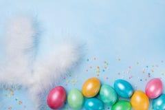 五彩纸屑、兔宝宝耳朵和五颜六色的复活节彩蛋在蓝色台式视图 看板卡复活节滑稽的问候 复制文本的空间 免版税库存照片