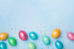 五彩纸屑和五颜六色的鸡蛋在蓝色台式视图 复活节问候横幅 复制文本的空间 免版税库存照片
