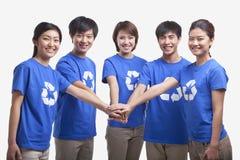 五微笑和佩带连续愉快的青年人一起回收标志T恤杉用手,演播室射击 免版税库存照片