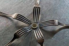 五把叉子和一枚硬币金属表面上 免版税库存图片