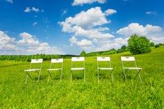 五把白色椅子在绿草连续站立 免版税库存图片