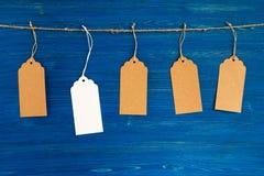 五棕色和垂悬在蓝色背景的一条绳索的白色白纸价牌或者标号组 免版税库存图片