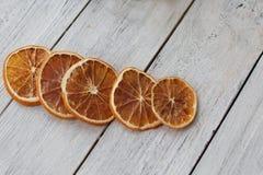 五烘干了在一个白色木背景特写镜头的芬芳桔子切片 免版税库存照片