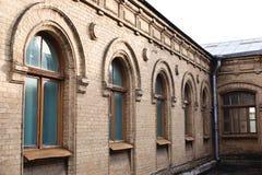 五葡萄酒成拱形在黄色砖墙壁的窗口  绿色-海在一褐红深红木的波浪玻璃的颜色 图库摄影