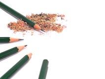 五被削尖的和有铅笔锯木屑的unsharpened绿色铅笔 免版税库存照片