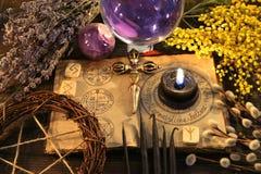 五角星形、诗歌、黑蜡烛和不可思议的花与开放书在巫婆桌上 免版税库存照片