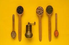 五谷、木匙子和成份的手动压榨机在黄色背景 谷物有机产品的概念,健康饮食 免版税库存照片