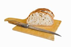 五谷面包在有一把面包刀的一个木切板切开了在白色背景 库存照片