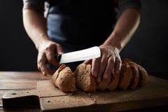 五谷面包投入了有拿着裁减的厨师的厨房木板材刀子 库存图片