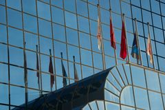 五面旗子和他们的反射在大厦 免版税图库摄影