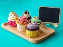 五颜六色与空的黑板和拷贝空间的自创杯形蛋糕您的文本的 在木盘子的杯形蛋糕在绿色背景 免版税库存图片