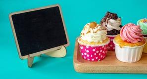 五颜六色与空的黑板和拷贝空间的自创杯形蛋糕您的文本的 在木盘子的杯形蛋糕在绿色背景 免版税图库摄影
