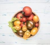 五颜六色各种各样有机蕃茄,在木碗的新鲜蔬菜农厂菜不同的品种在一土气backgro 免版税图库摄影