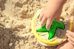 五颜六色和明亮的塑料黄色桶和绿色星在儿童` s手上在海沙/儿童` s戏剧背景与沙子 免版税库存图片