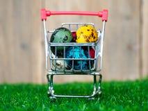 五颜六色在红色购物车的多复活节彩蛋在绿草背景是木板 库存照片