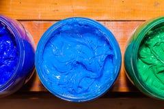 五颜六色塑料溶胶墨水玻璃无危险能在屏幕印刷品T恤杉的松林桌上 免版税库存照片
