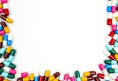 五颜六色抗生素压缩在白色隔绝的药片框架 库存照片