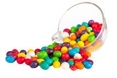 五颜六色洒在一白色backgr隔绝的玻璃的糖果 免版税库存图片