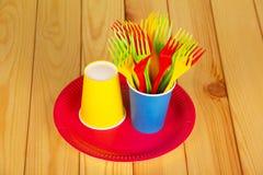 五颜六色的一次性碗筷:玻璃、板材和叉子在轻的木头 免版税库存照片