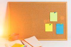 五颜六色的不同的贴纸在与笔记薄的在白色木桌上的corkboard和coffe pined,水平 3d概念图象计划回报了 吨 免版税库存照片