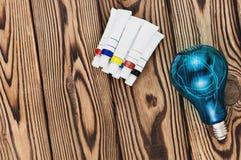 五颜六色的丙烯酸漆堆在闭合的容器的在电色的电灯泡旁边 免版税库存图片