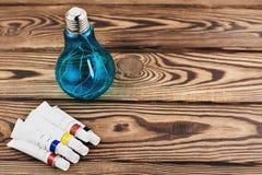 五颜六色的丙烯酸漆堆在闭合的容器的在电色的电灯泡旁边 库存照片