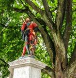 五颜六色的中世纪信使雕象的美好的城市街道视图在精心制作的喷泉顶部的在伯尔尼,瑞士 图库摄影