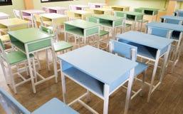 五颜六色的书桌在下午的教室 库存图片