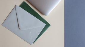五颜六色的信封和膝上型计算机在桌上 免版税库存照片