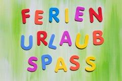 五颜六色的信件、德国词、概念假日和乐趣 库存图片