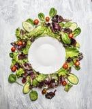 五颜六色的健康沙拉用黄瓜和蕃茄在白色空的板材附近,在浅灰色的木背景,顶视图 免版税库存图片