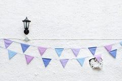 五颜六色的党下垂垂悬在与壁灯光的白色墙壁背景的旗布 最小的行家样式设计 免版税库存照片