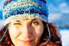 五颜六色的冬天盖帽的少妇眨眼睛与一只眼睛的 免版税库存照片