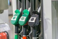 五颜六色的加油泵填装的喷管,在服务的加油站 免版税库存照片