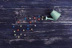五颜六色的发光的心脏从一把喷壶倾吐了,土气 浪漫背景为华伦泰` s天 免版税图库摄影
