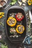 五颜六色的响铃充塞了在烹调在黑暗的土气厨房用桌背景的铁的辣椒粉胡椒罐 免版税库存照片