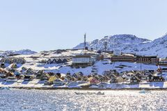 五颜六色的因纽特人房子行沿海湾的有雪山的 免版税库存图片