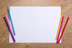 五颜六色的图画铅笔和白纸在木桌上 免版税库存照片