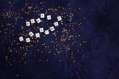 五颜六色的圆的糖果五彩纸屑和文本在黑背景的圣诞快乐Flatlay  免版税库存照片