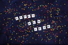 五颜六色的圆的糖果五彩纸屑和文本在黑背景的新年快乐Flatlay  免版税库存图片