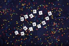 五颜六色的圆的糖果五彩纸屑和文本在黑色的圣诞快乐Flatlay  库存图片