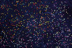 五颜六色的圆的糖果五彩纸屑Flatlay在黑背景的 免版税库存照片