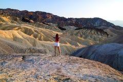 五颜六色的土坎环境美化与宽站立有吸引力的少妇开放胳膊在死亡谷美国感觉自由,女孩旅客 免版税库存图片