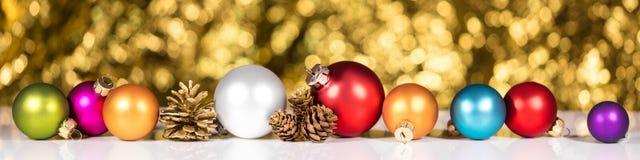 五颜六色的圣诞节球和冷杉球果在金黄backgr前面 免版税库存照片