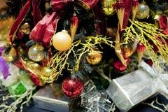 五颜六色的圣诞节装饰在与电灯泡的圣诞树下 免版税库存图片