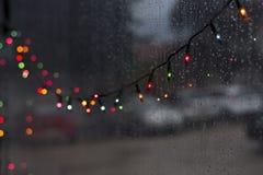 五颜六色的圣诞节bokeh带领了光夜雨天 免版税库存照片