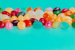 五颜六色的在土耳其玉色背景的豆甜糖果 2个所有时段小鸡概念复活节彩蛋开花草被绘的被安置的年轻人 关闭 复制空间 免版税库存图片