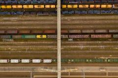五颜六色的在火车站的货车和桥梁鸟瞰图与物品的 库存照片