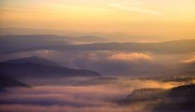 五颜六色的在视图的小山有薄雾的早&# 免版税库存照片