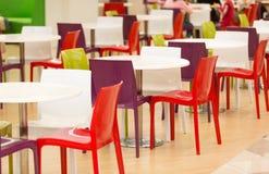 五颜六色的塑料椅子和桌在军用餐具 库存图片